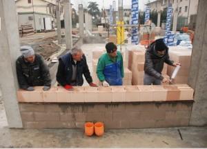 Una squadra di ragazzi trentini posa i mattoni rettificati per costruire il Centro servizi Val di Non
